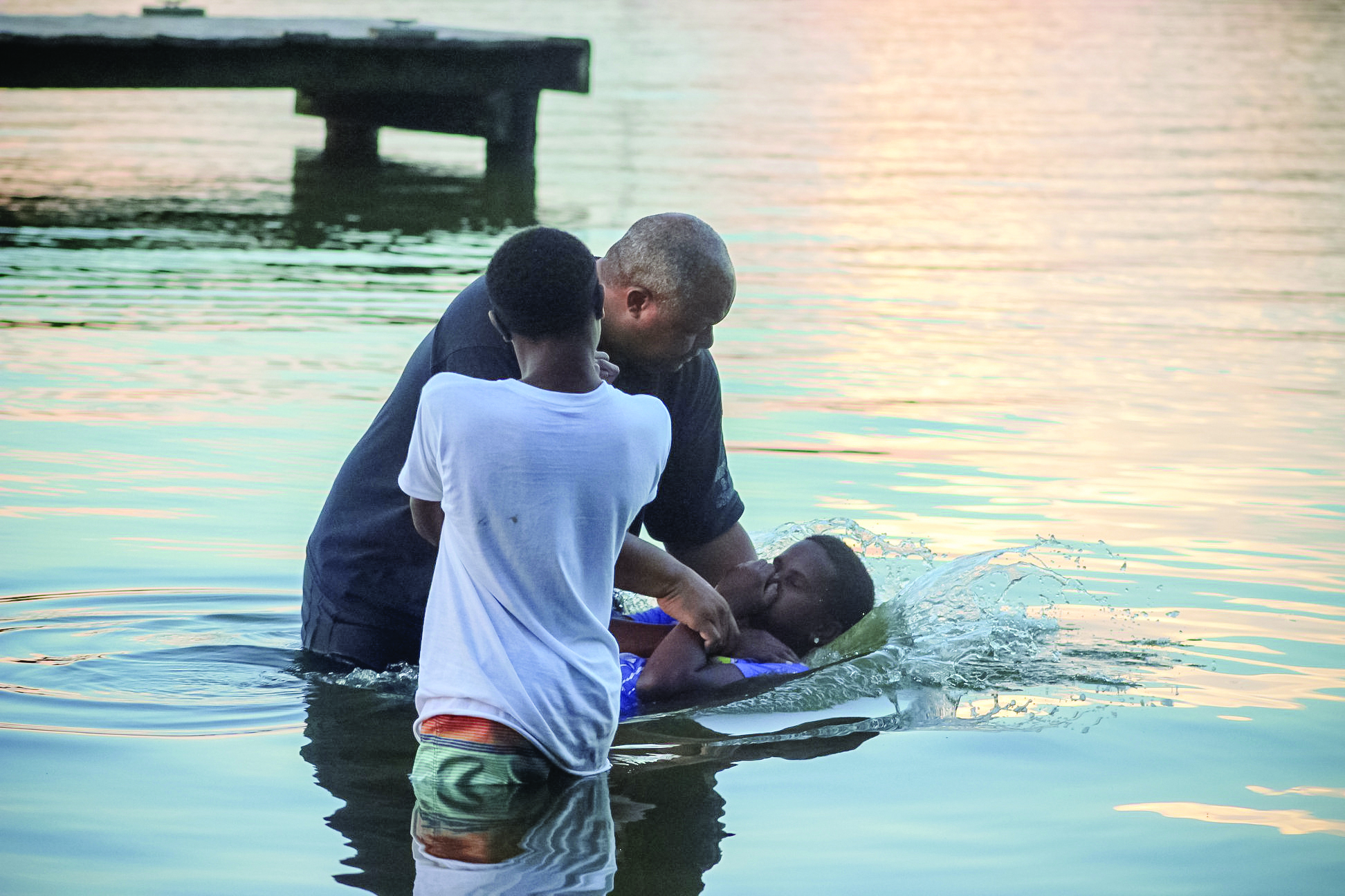 The Rev. Tim Warner baptizes two young boys at West River during Camp Hope.