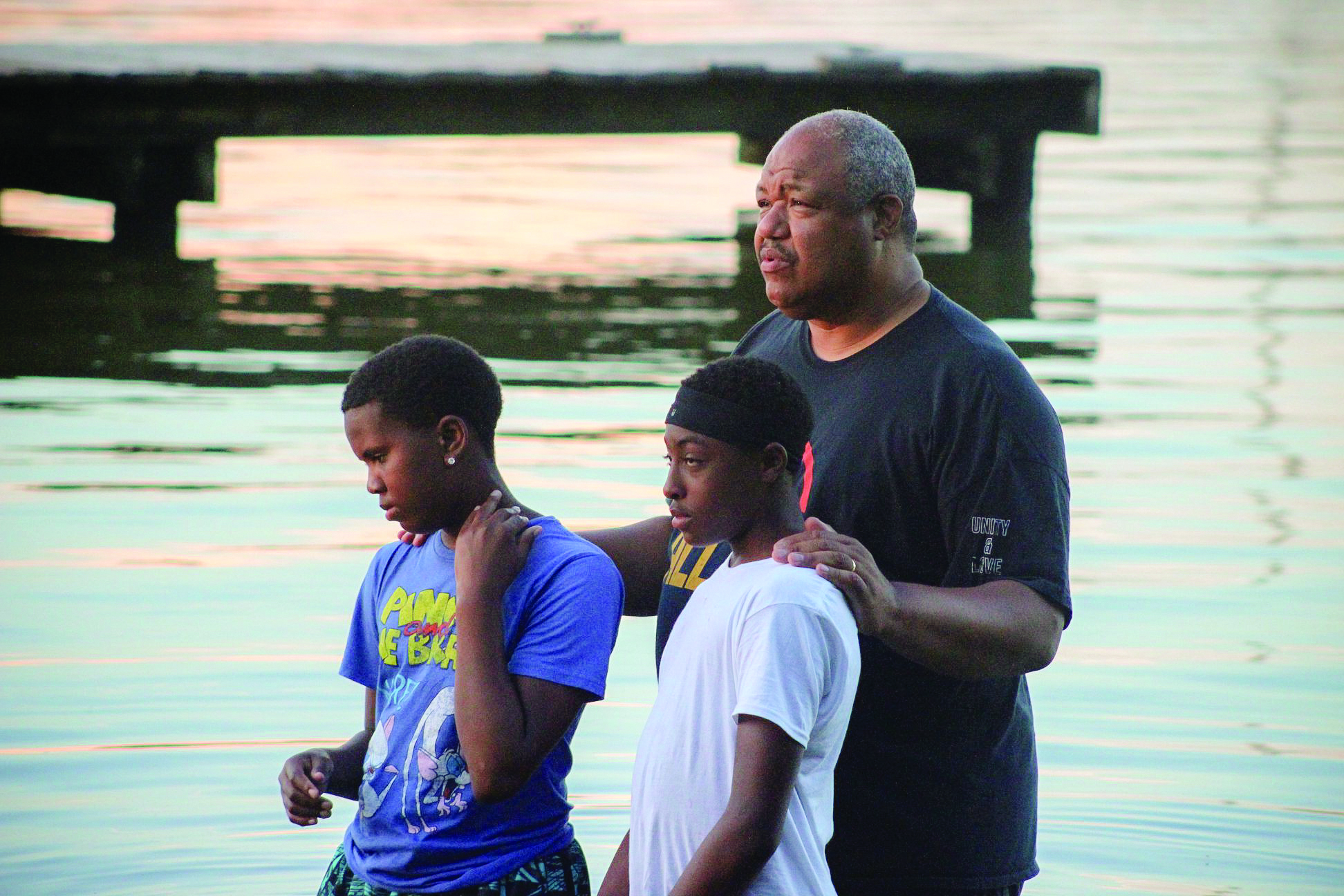 The Rev. Tim Warner, right, and in photo below left, baptizes two young boys at West River during Camp Hope.