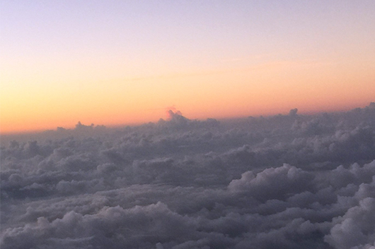 a sunset over the clouds from the view of a plane